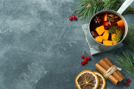 Christmas mulled wine with spices and fruit on the table. New year concept.