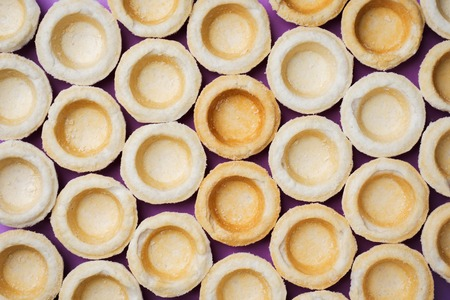 Empty shortbread tartlets laid out in a row. Abstraction concept in the color of the surface.