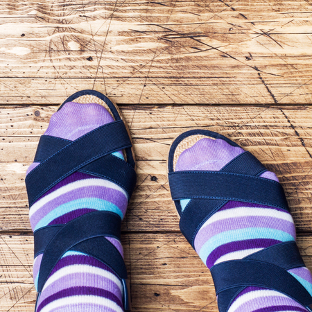 Womens feet in socks and sandals on wooden background