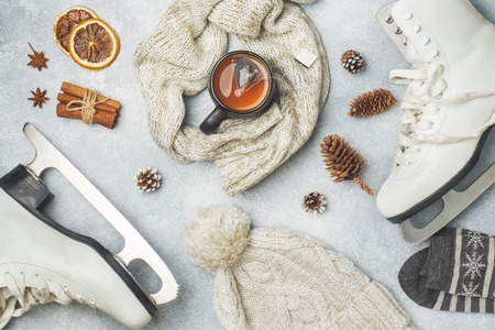 Winter vacation concept. Skates warm clothes, Cup of hot tea with fragrant spices on grey background