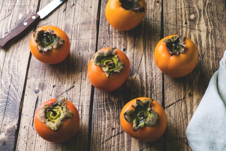 Fresh ripe persimmon on a wooden table.