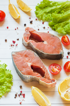 Raw red fish steak with lemon and spices and fresh vegetables on light background