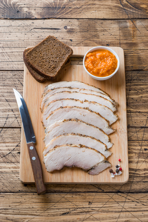 Pieces of smoked boiled pork on a wooden rustic Board with bread, sauces and spices on a wooden table. Фото со стока