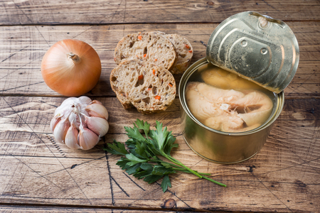 Ingredients for soup jar with pink salmon fish, pieces of bread, onion and garlic with greens on wooden background Stock fotó