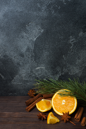 Christmas concept with cinnamon, fresh oranges and fir branches on a dark background with copy space Standard-Bild