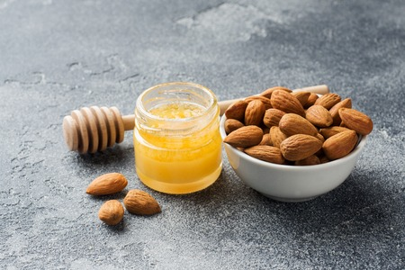 Almonds and a can of honey on the table. Selective focus. Copy space