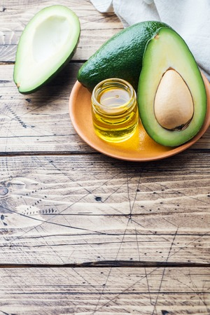 Avocado and avocado oil on wood background with copy space