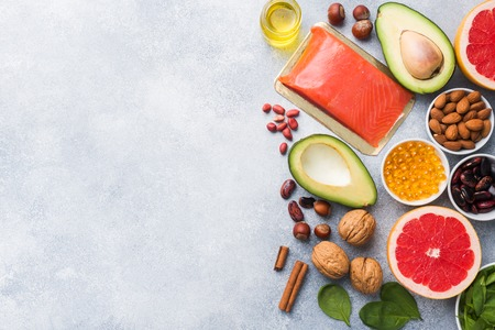 Healthy food antioxidant products: fish and avocado, nuts and fish oil, grapefruit spinach and oil on a gray concrete background. copy space. Stock fotó