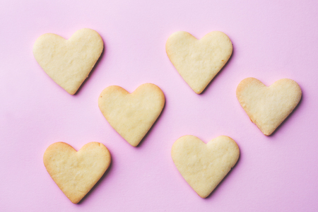 Homemade cookies in the shape of a heart on a pastel pink background. Copy space. Concept Valentines Day. Stock Photo