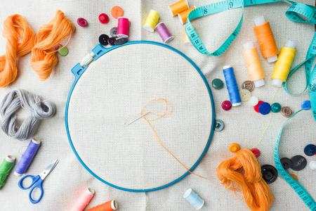 Ensemble de broderie. Tissu en lin blanc, cercle à broder, fils et aiguilles colorés. Espace de copie