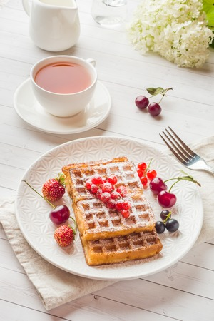 Homemade waffles with summer berries on a plate. A Cup of tea on a light table. Selective focus. Banque d'images