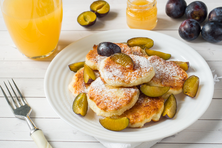 Cheese pancakes in powdered sugar with fresh plums on a plate.