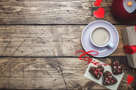 Konzept Valentinstag. Tasse Kaffee und Kekse auf einem Holztisch. Grußkarte Platz kopieren Standard-Bild