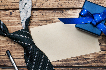 Fathers Day Concept. Striped tie and a gift on wooden  with copy space