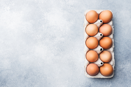 Brown raw Chicken eggs in factory packaging on grey background Copy space 스톡 콘텐츠