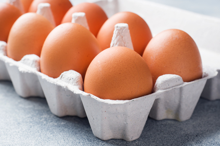 Brown raw Chicken eggs in factory packaging on grey background
