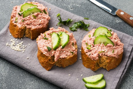 Sandwiches with chicken pate and cucumber on dark table