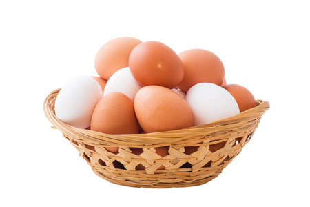 Chicken eggs in basket on isolated white background