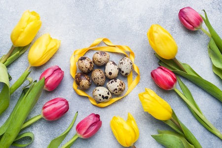 Bright flowers tulips and quail eggs on stone background. Spring and Easter holiday concept with copy space.