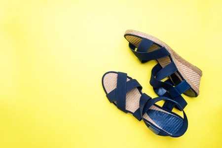 Blue sandals on yellow background with copy space. concept summer vacation. Flat lay.