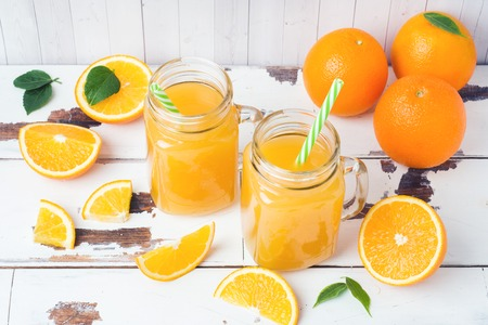 Orange juice in glass jars and fresh oranges on a white wooden rustic background