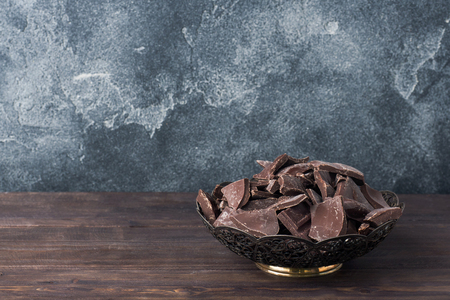 Pieces of crushed dark chocolate in a Plate on a dark background. copy space