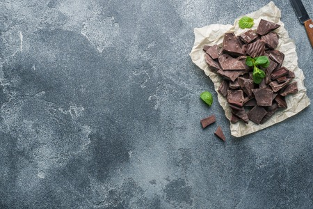 Pieces of crushed dark chocolate with mint leaves dark textured background with copy space