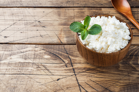 Homemade cottage cheese with mint in a bowl on old wooden table Copy space. Stock Photo