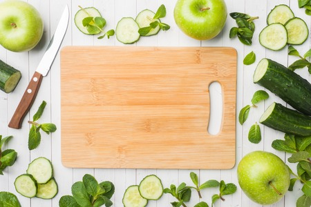 Green cucumber mint Apple on the table. The concept of diet and vegetarianism. Copy space. Empty wooden cutting Board Banco de Imagens