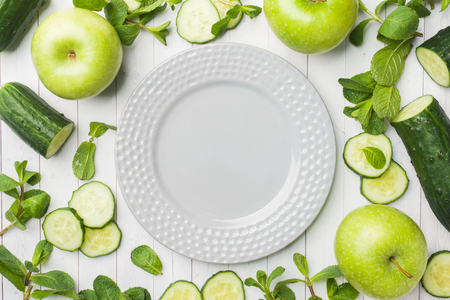 Green cucumber mint Apple on the table. The concept of diet and vegetarianism. Copy space. Empty grey plate