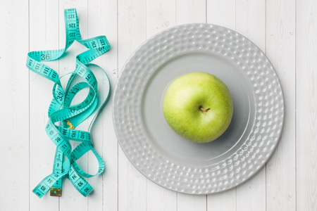 Diet concept. Green Apple on a plate and tape centimeter on a white table