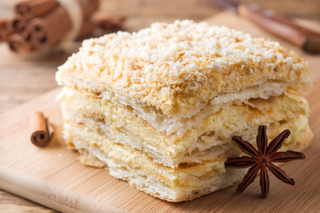Layered cake with cream Napoleon millefeuille vanilla slice with cinnamon and anise on wooden background