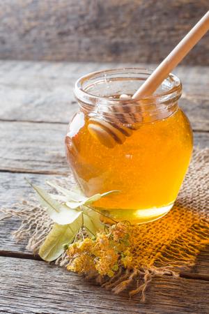 Glass jar of honey, Linden flowers on wooden background,