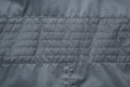 texture of black fabric stitched with threads. Jacket detail. Stock Photo