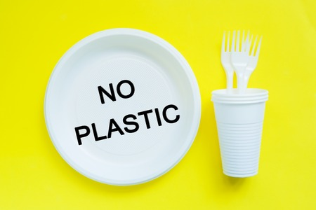 Disposable plastic tableware on bright yellow background with copy space concept of protest and the words No Plastic