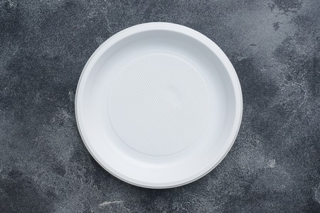 Disposable plastic tableware plates on dark background with copy space