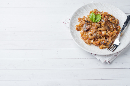 Stewed cabbage with mushrooms on white wooden