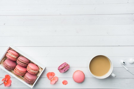 Cup of coffee, macaroon cookies in a box, flowers on a white
