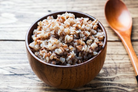 Boiled buckwheat in a wooden bowl on the village table