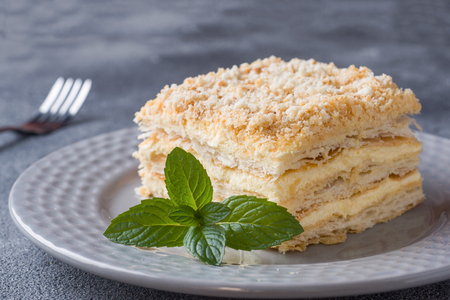 Layered cake with cream Napoleon millefeuille vanilla slice with mint on dark