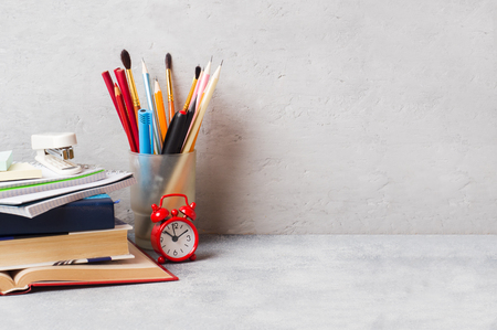 School supplies, books notebooks pencils on grey background with copy space