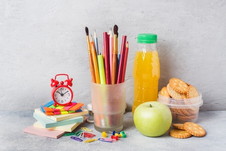 School supplies and Breakfast crackers, orange juice and fresh Apple on the grey table with copy space. concept school Stock Photo