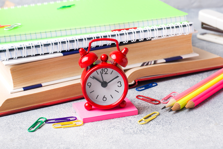 School supplies, clock book notebooks pencils on grey background with copy space