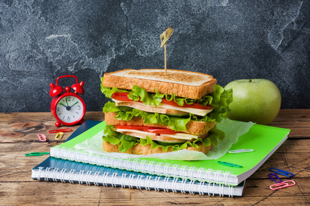 Healthy lunch for school with sandwich, fresh apple. Assorted colorful school supplies. Copy space Zdjęcie Seryjne