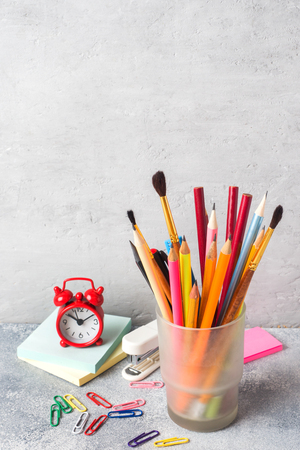School supplies, a set of pencil markers in a glass on a gray table with a copy of space. Concept school Stock Photo