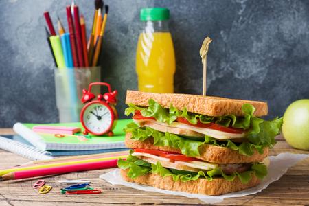 Gesundes Mittagessen für die Schule mit Sandwich, frischem Apfel und Orangensaft. Verschiedene bunte Schulmaterialien. Platz kopieren Standard-Bild