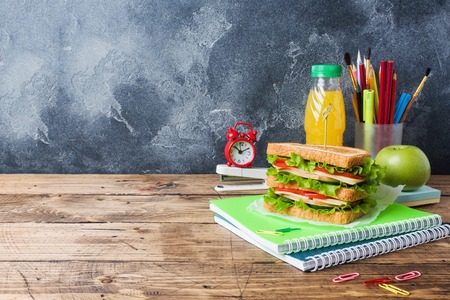 Healthy lunch for school with sandwich, fresh apple and orange juice. Assorted colorful school supplies. Copy space