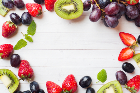 Fresh fruit strawberry kiwi grapes on white table with copy space