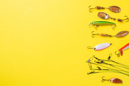 Fishing hooks and baits in a set for catching different fish on a yellow background with copy space. Flat lay,