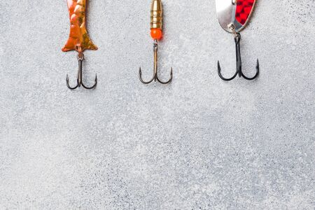 Fishing hooks and baits in a set for catching different fish on a grey background with copy space. Flat lay,